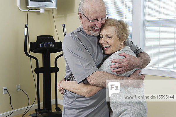 Senior couple hugging near exercise equipment after a workout