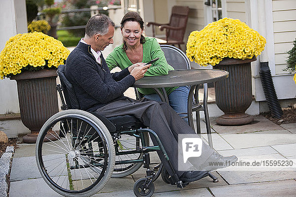 Woman and her husband in a wheelchair sitting at a cafe and using a digital tablet