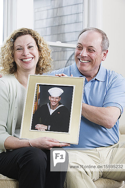 Portrait of a mature couple holding picture of their son working in the military.