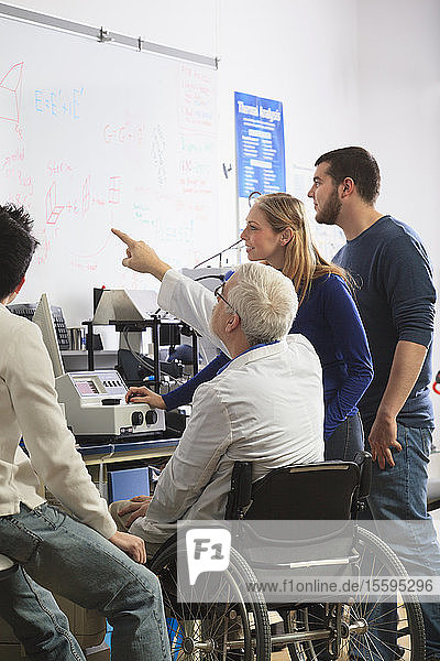 Professor with muscular dystrophy and engineering students reviewing analyzer results on white board in a laboratory