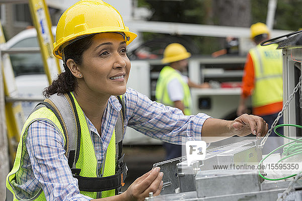 Hispanic female utility worker working with line amplifiers at site