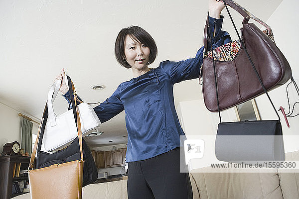 Portrait of a mid adult woman showing off purses