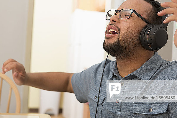 Happy African American man with Down Syndrome listening to music and singing with headphones at home