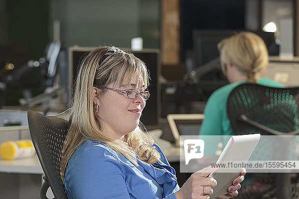 Young woman with Down Syndrome working on a tablet in an office