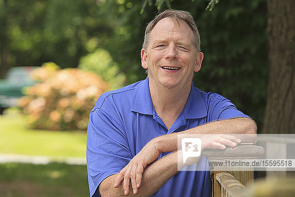 Man with Cerebral Palsy and dyslexia relaxing on his fence