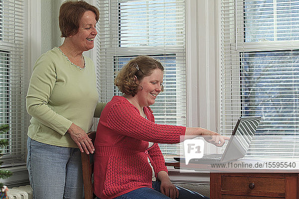 Young woman with Autism and her mother using their laptop