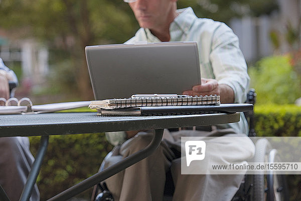 Businessman with spinal cord injury working on a laptop