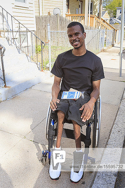 Man in a wheelchair who had Spinal Meningitis on the city street