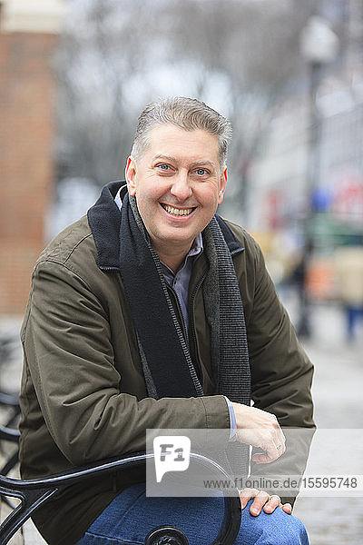 Portrait of a man sitting on a bench and smiling  Boston  Suffolk County  Massachusetts  USA Portrait of a man sitting on a bench and smiling, Boston, Suffolk County, Massachusetts, USA