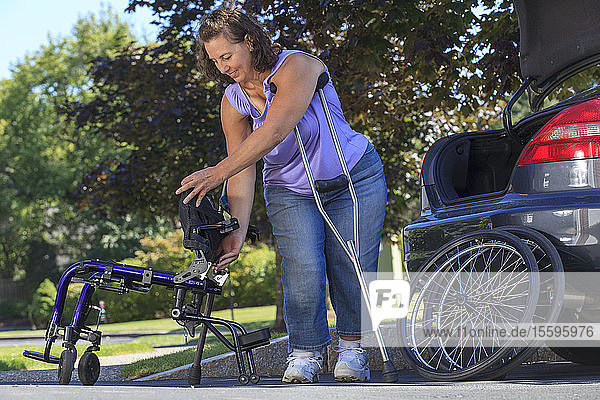 Woman with Spina Bifida using crutches to take wheelchair apart for traveling in the car