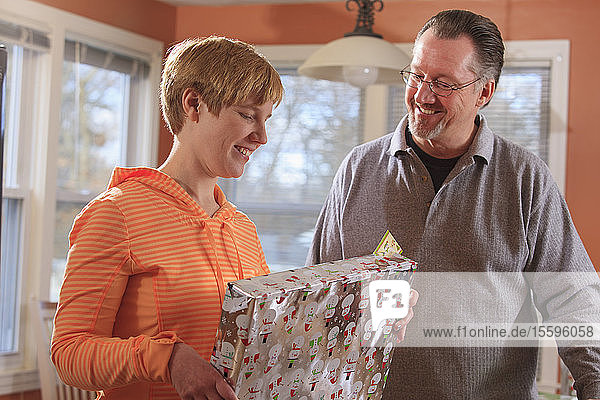 Young woman with visual impairment looking at a holiday gift with her Dad