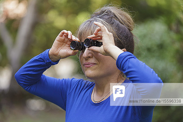 Woman with visual impairment using special glasses to see in park