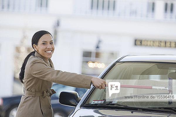 Hispanic woman washing the windshield of a car