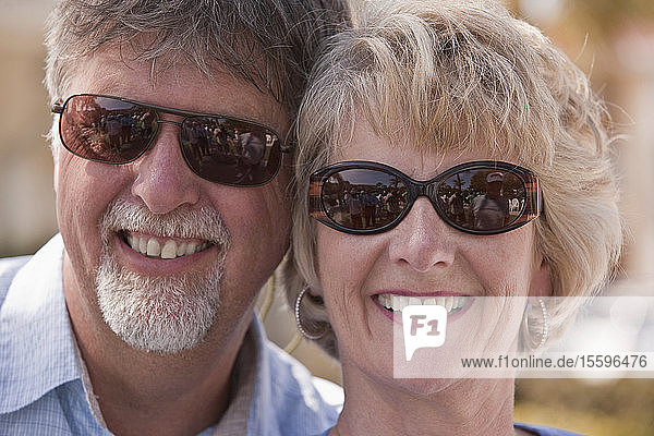 Close-up of a couple smiling with reflection of shuffleboard game in sunglasses