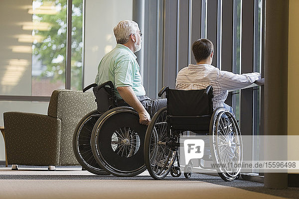 Mature man with Muscular Dystrophy and a young woman sitting in wheelchairs in a library