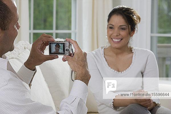 Hispanic man taking a picture of a Hispanic woman