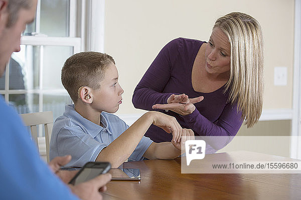 Mother communicating with son in American Sign Language 'School' at home