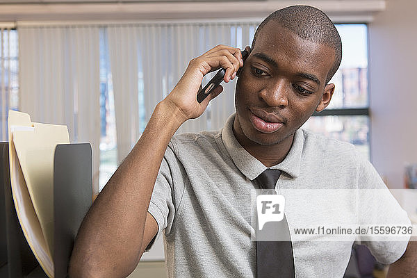 African American man with Autism talking on cell phone in an office