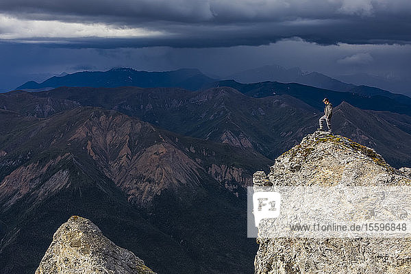A hiker stands in the sunshine on top of Sukakpak Mountain while storm clouds approach over the Brooks Range; Alaska  United States of America