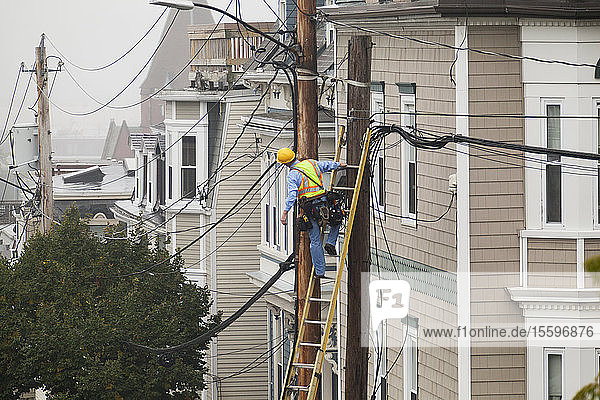 Cable lineman assessing cable distribution wiring on poles in the city