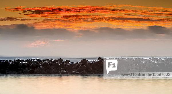 Sunrise over Lydgate Park and the ocean from the coast of Kauai with a breakwater; Kapaa  Kauai  Hawaii  United States of America