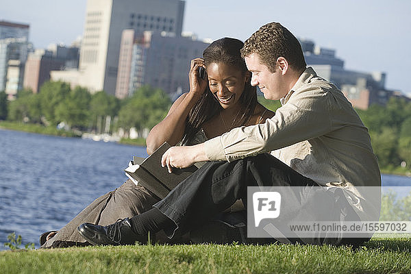 Mid adult couple sitting in a park reading a book  Boston  Massachusetts  USA