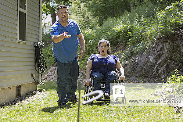 Woman with Spina Bifida in a wheelchair playing horseshoes with her husband
