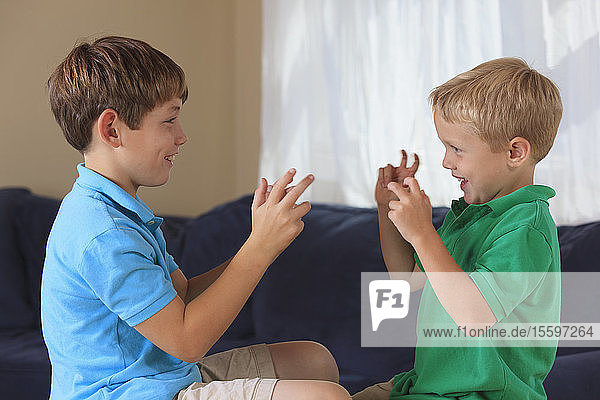 Boys with hearing impairments signing 'basketball' in American sign language on their couch