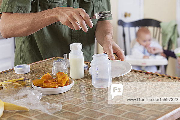 Father preparing baby's meal