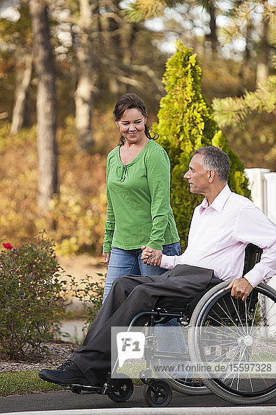 Woman using sidewalk with husband in wheelchair with spinal cord injury