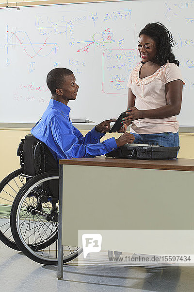 Two engineering students  one in wheelchair  looking at electronic tablet in a classroom