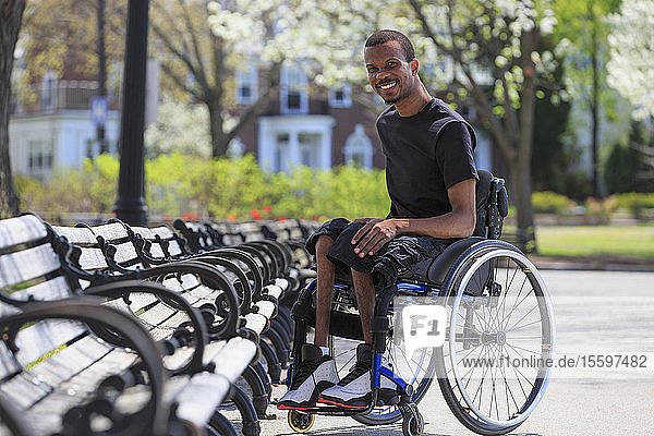 Man in a wheelchair who had Spinal Meningitis sitting near a park bench