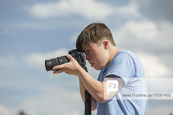Young man with Down Syndrome photographing with camera