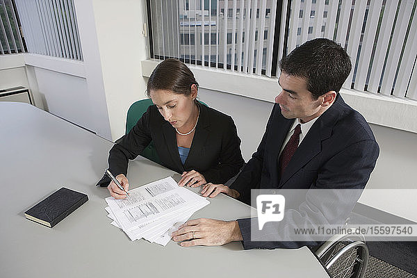 High angle view of a Businessman with spinal cord injury and a businesswoman working in an office
