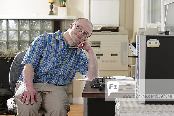 Man with Down Syndrome sitting at his computer in an office