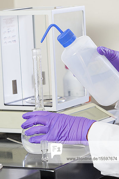 Laboratory scientist washing solid reagent into a water sample in a flask