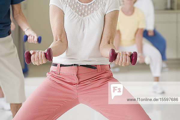 Mid section view of a senior woman exercising with hand weights