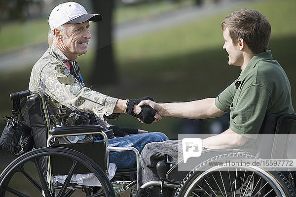 Side profile of a mature war veteran shaking hands with a young man