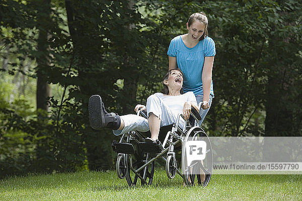 Young woman pushing her mother sitting in a wheelchair and laughing
