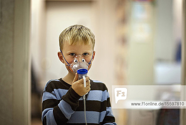Portrait of young boy with oxygen mask.