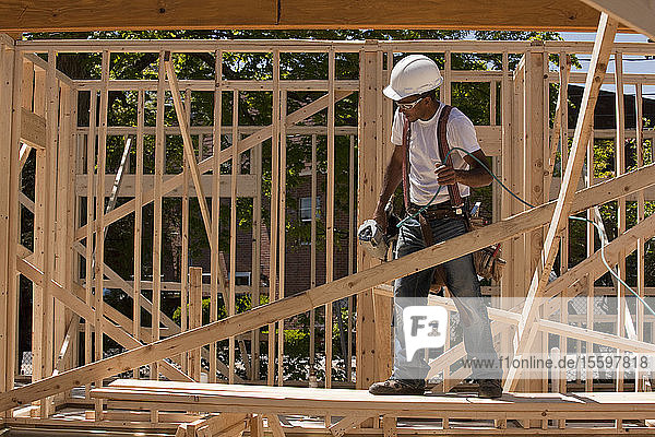 Carpenter standing at a construction site holding a nail gun