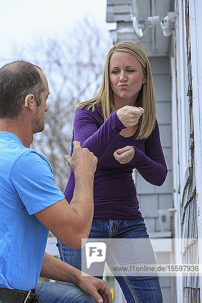 Homeowner communicating with home repairman in American Sign Language  saying 'Replace' and 'Part of it'
