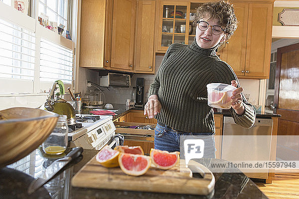 Woman with Sjogren-Larsson Syndrome putting grapefruit in a container