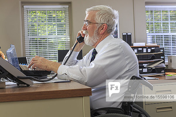 Man with Muscular Dystrophy in a wheelchair on the phone in his office
