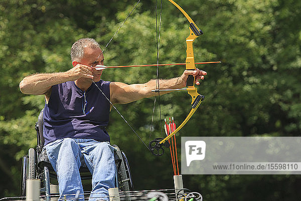 Man with spinal cord injury in wheelchair aiming his bow and arrow for archery practice