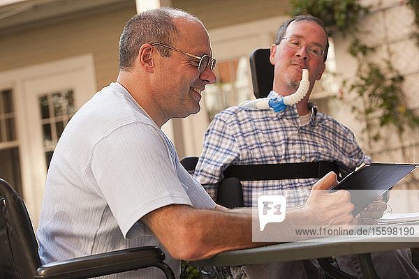 Businessman with Duchenne muscular dystrophy and a man with Friedreich's Ataxia working at a cafe