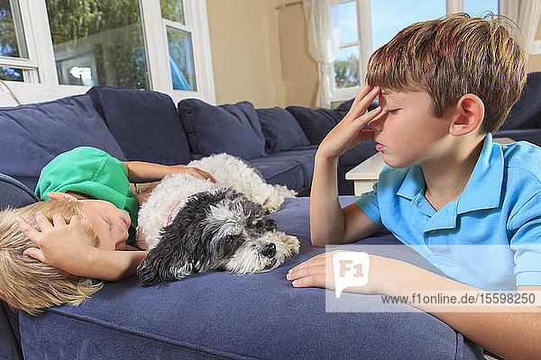 Boys with hearing impairments signing 'sleep' in American sign language on their couch
