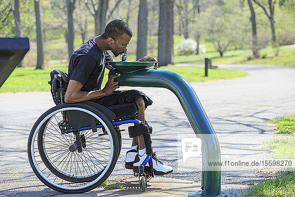 Man in a wheelchair who had Spinal Meningitis using a public water fountain
