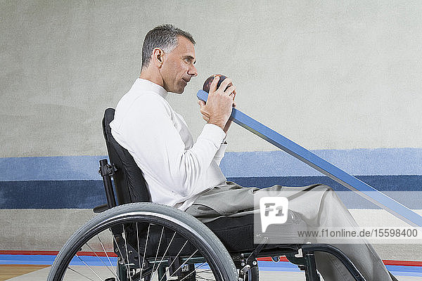 Side profile of a mature man with a Spinal Cord Injury sitting in a wheelchair and playing ten pin bowling