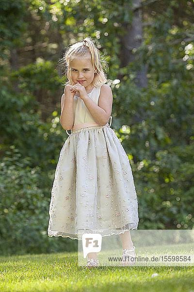 Portrait of a cute little girl standing in a garden